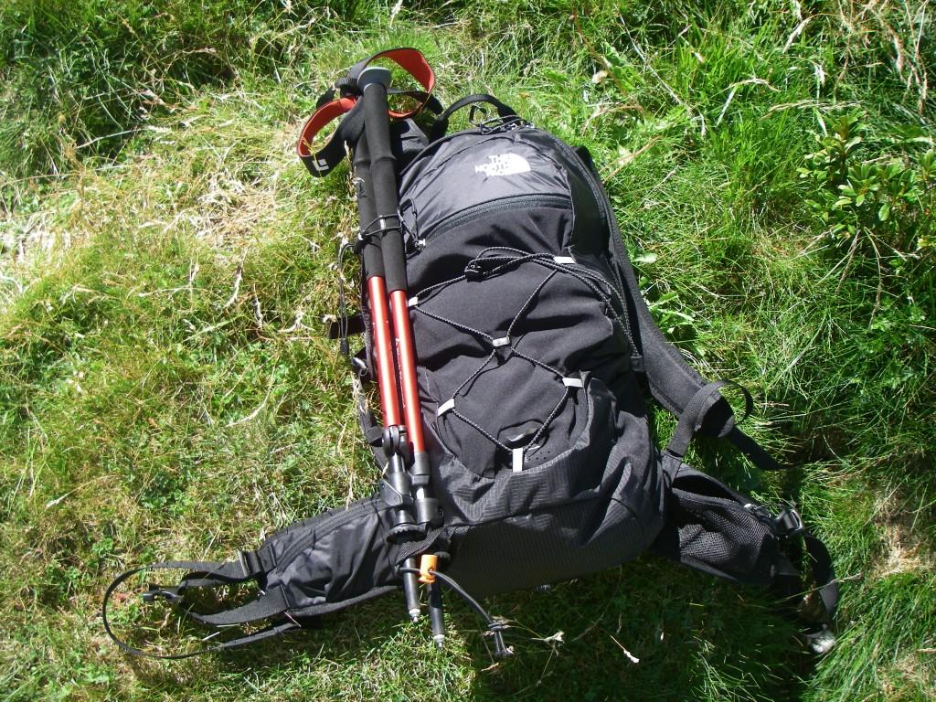 Vue de l'extérieur du sac avec les 2 poches sur la ceinture dont une en mesh, le porte-matériel avec l'élastique et la fixation pour les bâtons. À noter aussi la poche extérieure en tissu stretch